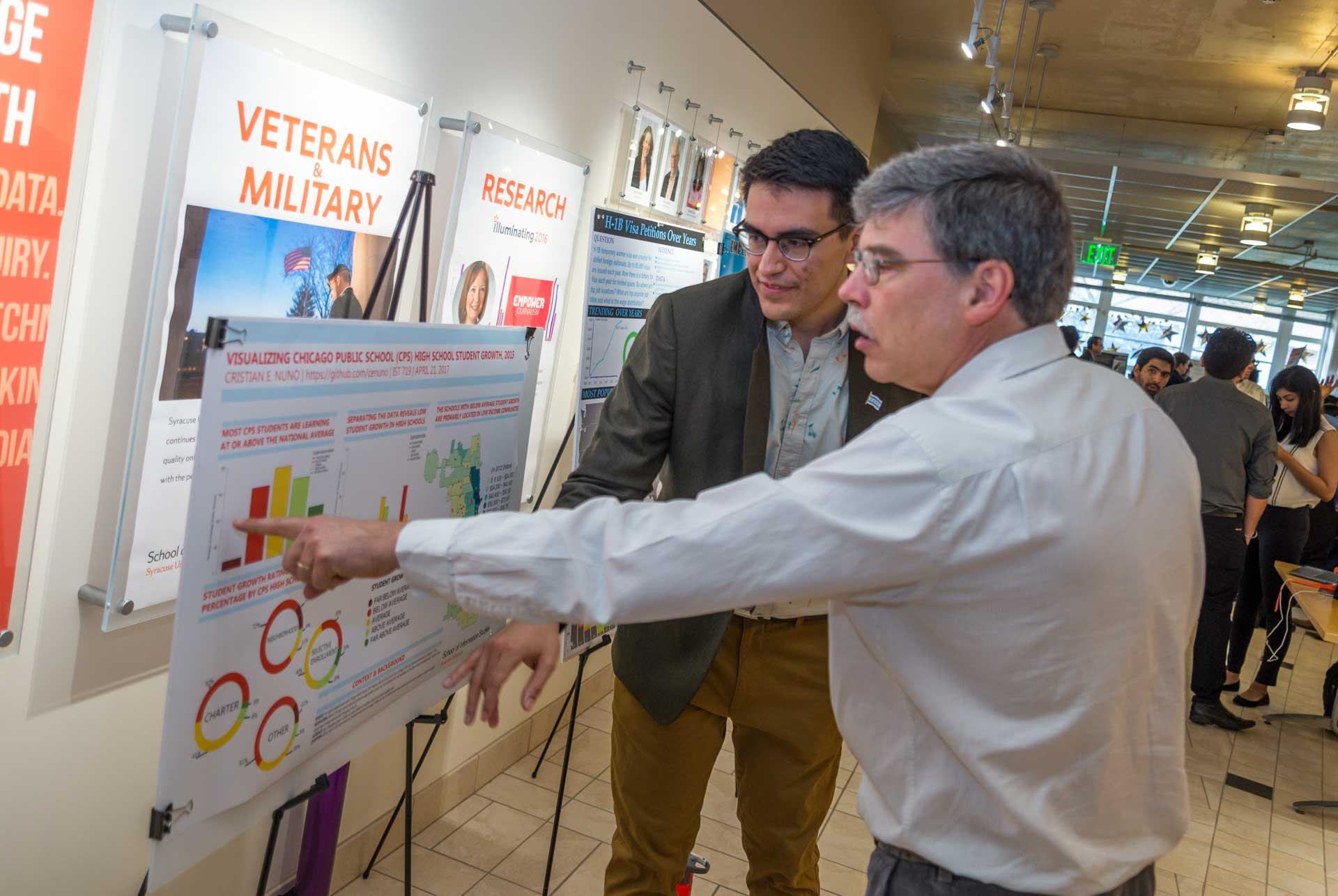 Faculty members looking at student posters