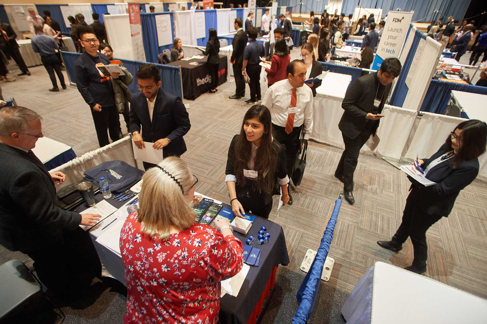 A student speaks with a recruiter at an iSchool career fair