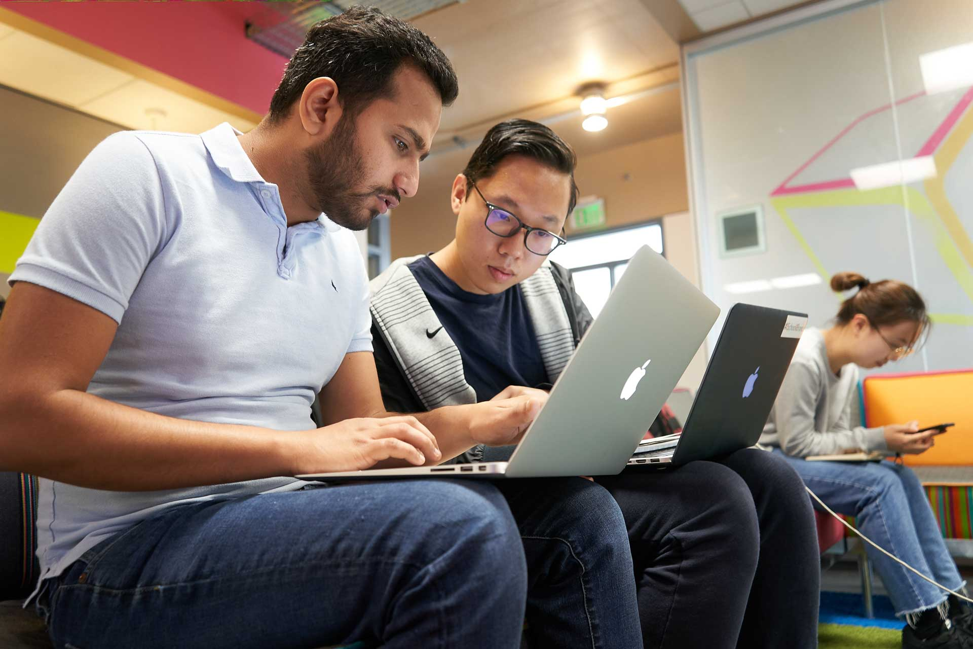 Two students working in an iSchool workspace