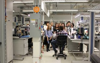 Students listening to employee at lab