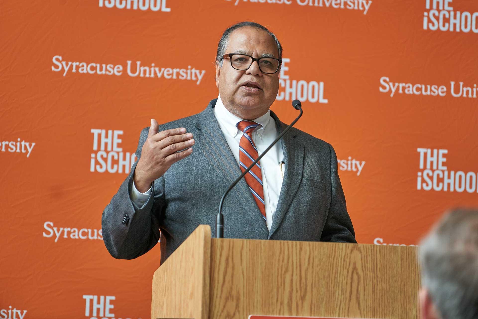 Dea Raj Dewan speaking at a podium