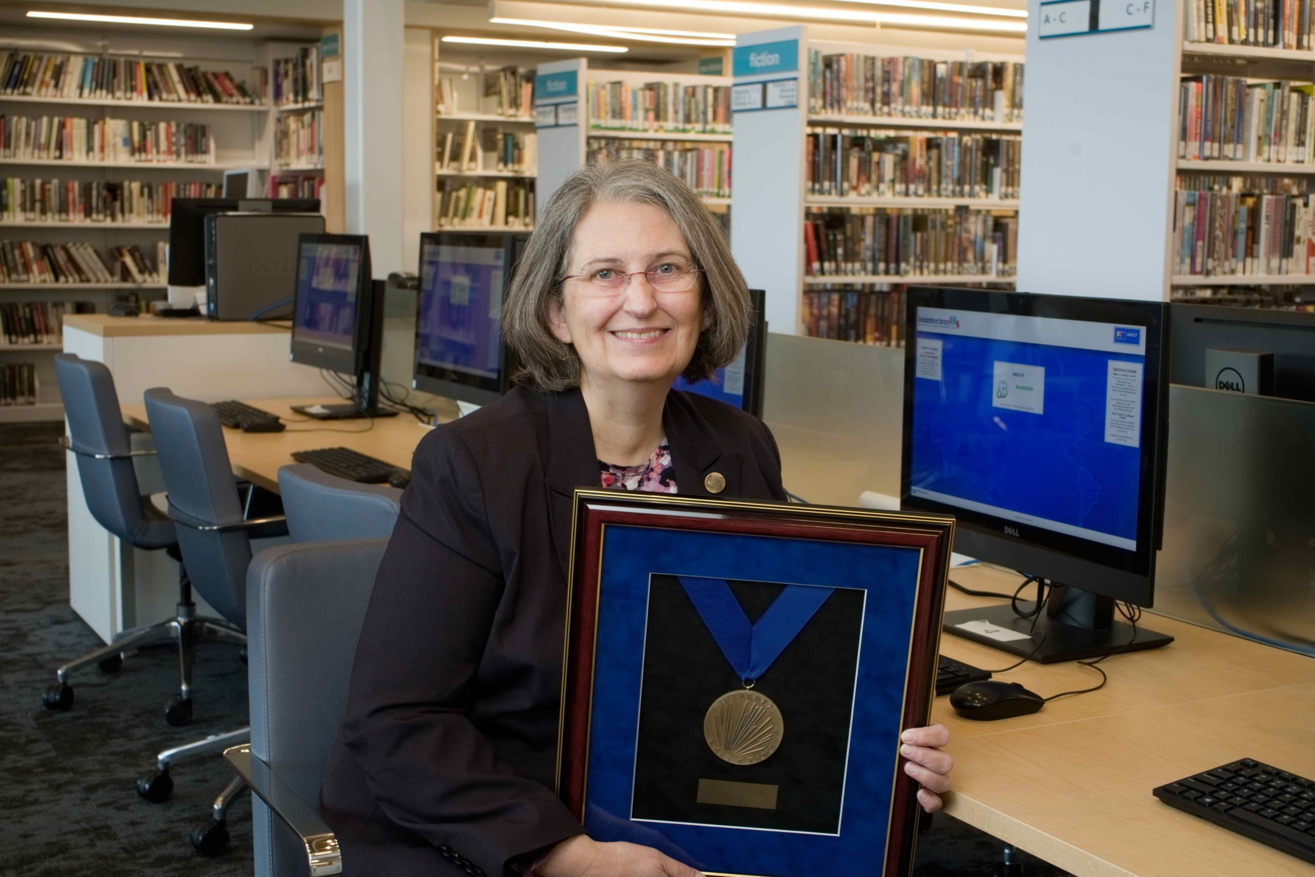 Jean Armour-Polly sits in library with her award
