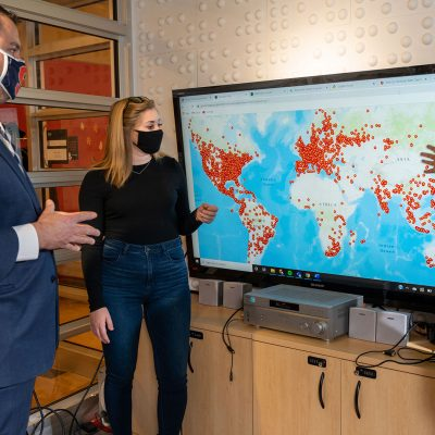 Student and faculty in NEXIS Lab pointing at data map